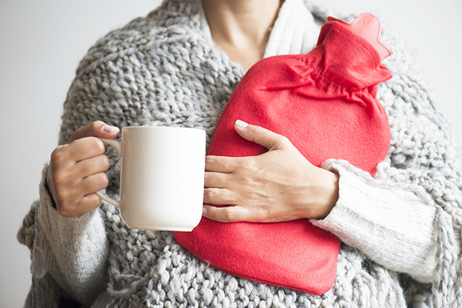 Lady holding a hot tea and hot water bottle rugged up